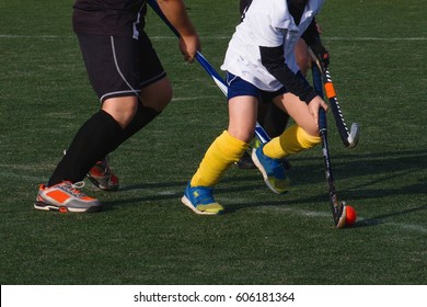 Children playing field hockey competitively. Two defenders unsuccessfully chasing an attacker with ball.