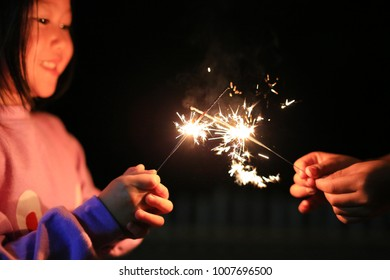 Children are playing with fire sparklers on the festival.