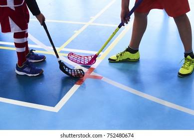 Children playing floorball. The start of a match showing two players with their sticks and the ball starting the kick-off
