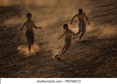 Children playing football at the countryside.