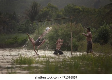 Children Playing Football on water in rural. (Focus on the ball to kick.)