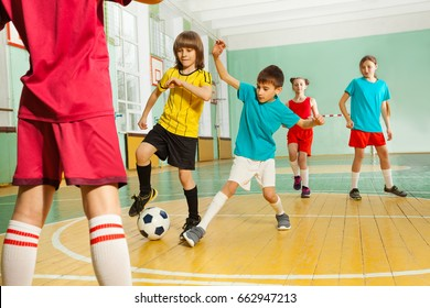 Children playing football in school gymnasium