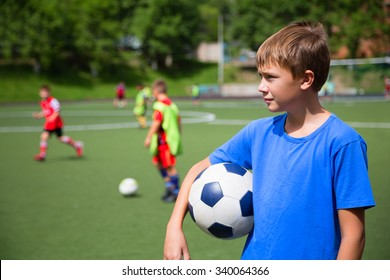 Children playing football in a stadium on a summer day