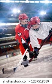 children playing hockey on ice