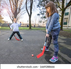 children are playing hockey on the street