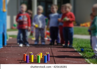 Children playing with homemade, do-it-yourself educational toys, tube bowling. Learning through experience concept, gross and fine motor skills, educational approach concept.