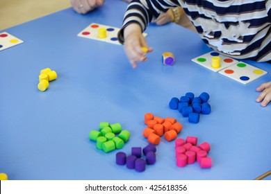 Children playing with homemade, do-it-yourself educational toys, arranging and sorting colors. Learning through experience concept, intelligence development, educational approach concept.