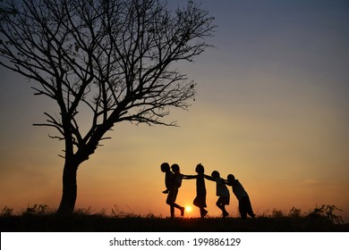 Children playing joyfully In the Sunset.