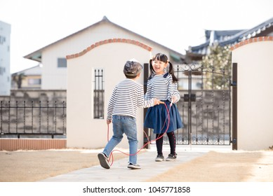 Children playing jump rope in the garden