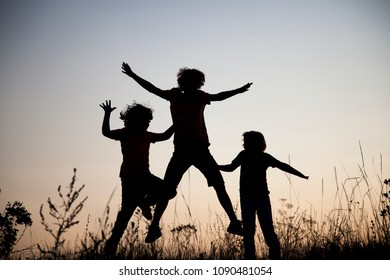 Children playing jumping on summer sunset meadow silhouetted.