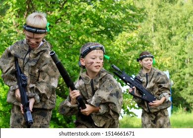 Children playing in lasertag shooting game in open air. Weapon in the hands of people. War simulation.