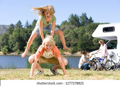 Children playing leapfrog in countryside on motor home vacation