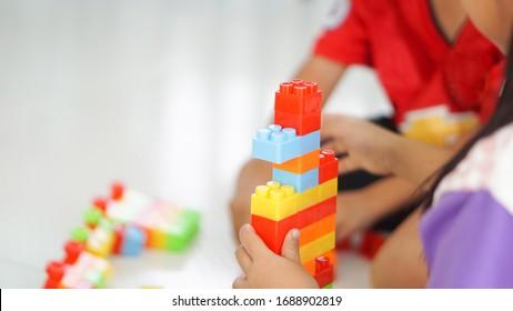 Kinder, die mit Lego-Steinen spielen. Kleines Mädchen und lustiger, heiliger Junge mit pädagogischen Spielzeugblöcken. Kinder spielen in der Tagesbetreuung oder Vorschulzeit.