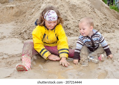 Children playing in the mud and they are happy