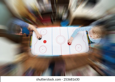 Children playing on air hockey at home