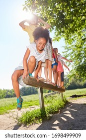 Children are playing on a balance beam in the park on the trim path