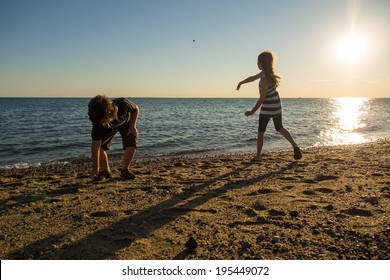 Children playing on the beach in Cape Cod at sunset