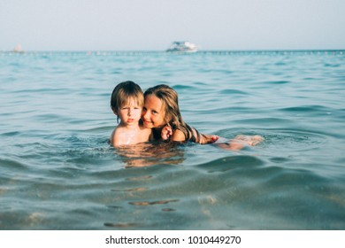 Children are playing on the beach on summer time. Lifestyle. Vacations on seashore. Girl and boy in water in sunset time.