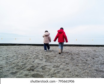 Children playing on the beach in winter, Lake Maggiore, Ispra, Lombardy, Italy