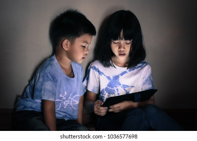 Children playing on tablet. Asian siblings sit in living room and looking with pc tablet together, in darkness room dim light background bright screen reflex on kid's faces.