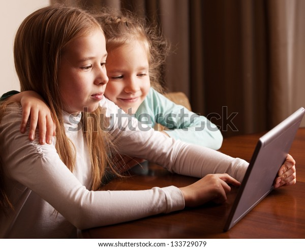 Children playing on tablet. Kids looking at computer
