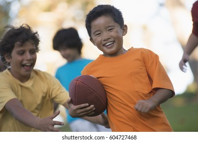 Children playing outdoors in summer, one running with a ball,