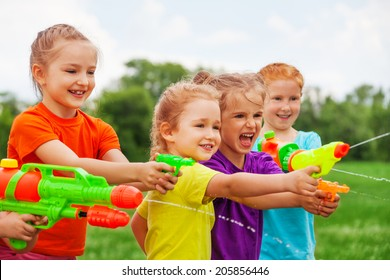 Children playing outdoors with water guns on a beautiful sunny day