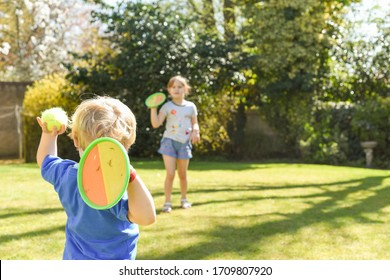 Children playing outside a brother and sister play a ball game in a garden