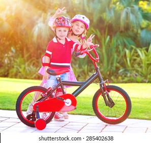 Children playing in the park, cheerful brother and sister having fun on bicycle, enjoying summer time, happy active childhood