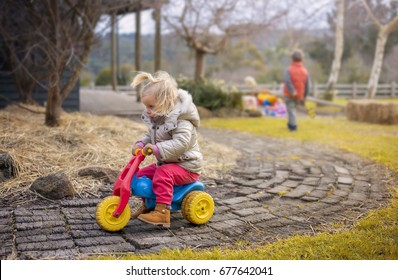 Children playing in the park. A Little girl riding bikes
