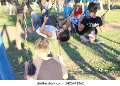 children playing in the park playground on a sunny and green day