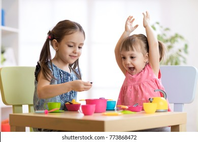 Children playing with plastic tableware at home or daycare center
