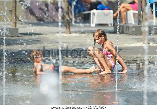 Children playing in a puddle and fountains in the park in hot weather