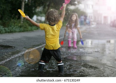 Children playing in a puddle. Toned