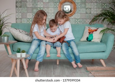 Children playing with retro photo camera sitting on a sofa