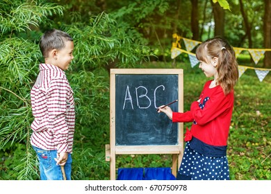 Children are playing at school. Students teach an alphabet on a school board. The concept is back to school.