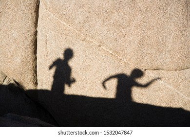 children playing with shadow at a rock in Joshua tree national park, USA