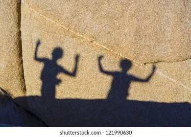 children playing with shadows on a rock in Jushua Tree National park