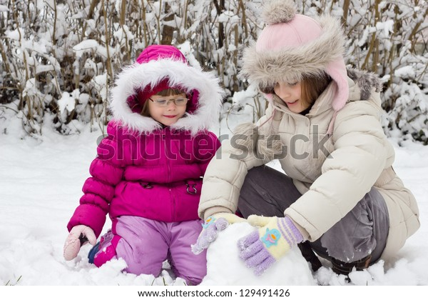 children playing in snow, best focus on the fur hats