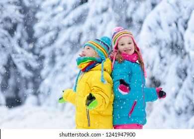 Children playing with snow in winter. Little girl and boy in colorful jacket and knitted hat catching snowflakes in winter park on Christmas. Kids jump in snowy forest. Snow ball fight for children.