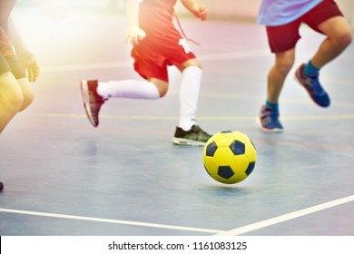 Children playing soccer with yellow football indoors
