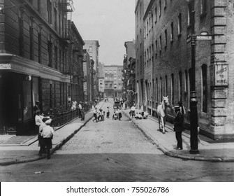 Children playing in the street on Minetta Lane, Greenwich Village, New York City, 1923. A man leads a horse to a building with a sign 'Horses to hire'. Further up the lane is a horse-drawn carriage