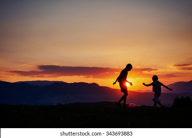 Children playing at sunset