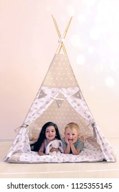 Children playing in the teepee.  Copy space