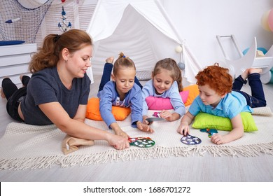Children playing with their teacher in the kindergarten