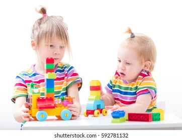 children playing together at daycare with educational toys indoors. girl and boy in preschool age building toy tower