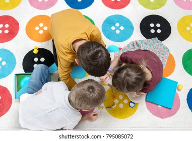 Children playing together with a play on the carpet and having fun together