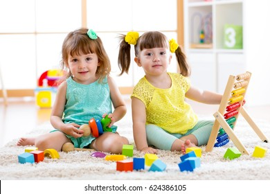 Children playing together. Toddler kid and baby play with blocks. Educational toys for preschool and kindergarten child. Little girls build block toys at home or daycare.