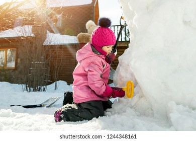 Children playing together in yard after snowfall in winter. Group of kids bilding figures and snowman with shovels and other tools outdoors. Child winter activities