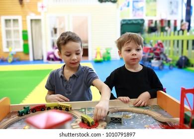 Children playing with toy railroad in kindergarten